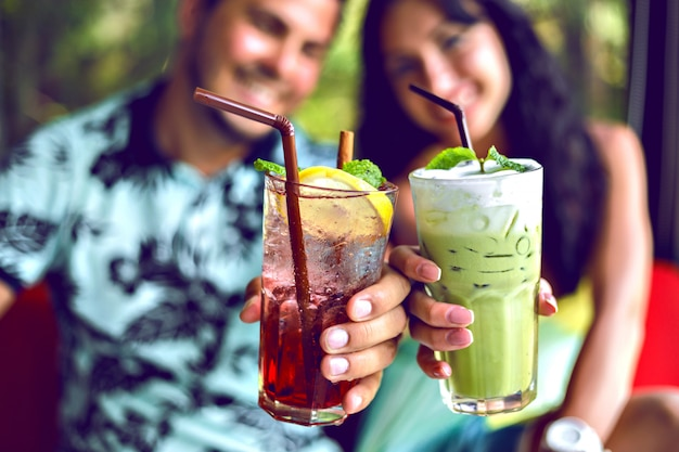 Close up shot of young smiling couple enjoy their drinks, making cheers to camera, matcha latte and berry lemonade, cocktails on party, toned bright colors.