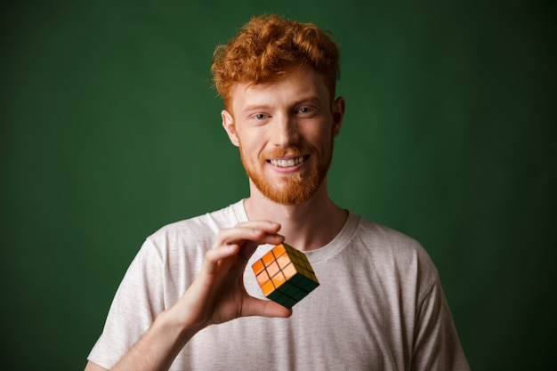 Close-up shot of young smiling readhead bearded man, holding rubik's cube