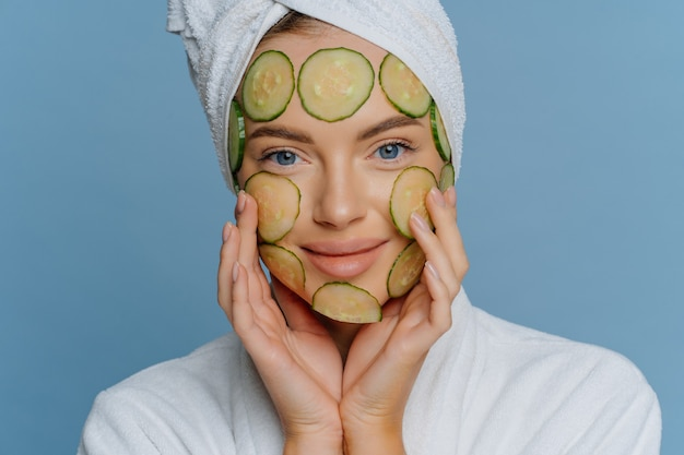 Close up shot of young woman applies cucumber slices on face for healthy skin