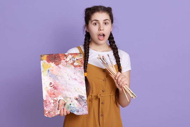 Close up shot of young woman artist holding color palette and paint brush in hands