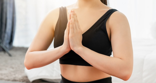 Close up shot of a young woman doing yoga exercises in the living room at home
