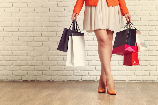 Close up shot of young woman leg carrying colorful shopping bags