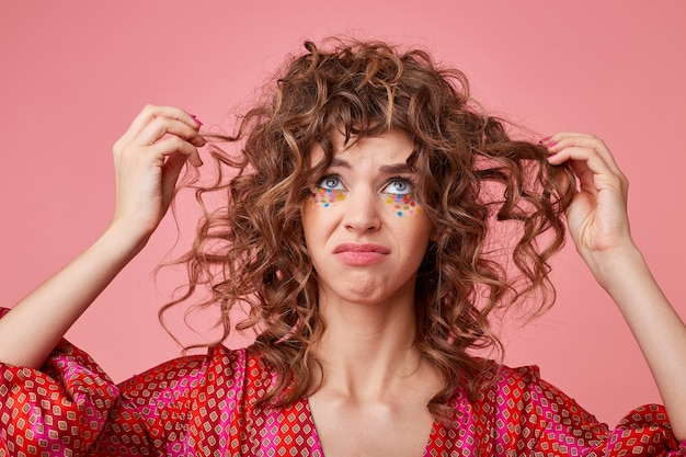 Immagine ravvicinata di giovane donna che guarda in alto, tirando i capelli ricci ed essendo triste, facendo smorfia, mostrando delusione