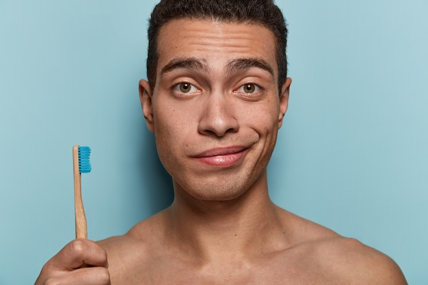 Close up shot of youngster with healthy skin, strong body, holds toothbrush, going to have morning hygienic procedures, stands against blue wall. hygiene, dental care and beauty concept