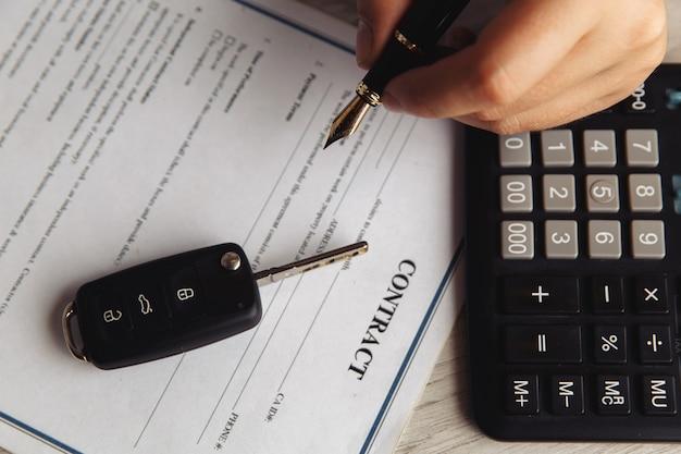 Крупным планом выстрелы руки клиента, подписывающего форму аренды автомобиля. вид сверху