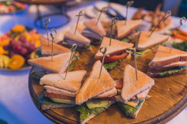 ケータリングパーティーの盛り合わせにさまざまなサンドイッチの三角形のショットをクローズアップします。