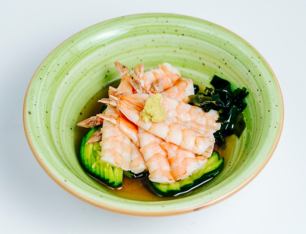 Close up of shrimp miso soup served in apple green bowl in white background