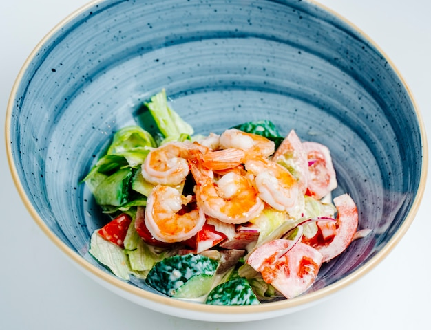 Close up of shrimp salad with vegetables and mayonnaise in blue bowl