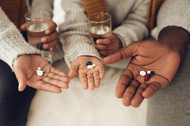 Close up sick african american family drinking pills.