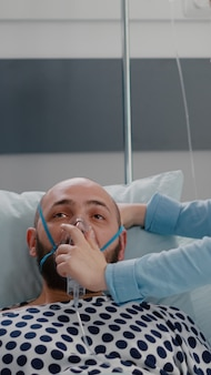 Close up of sick man patient resting in bed while doctor putting oxygen mask monitoring respiratory illness in hospital ward during healthcare emergency. physician analyzing heartbeat pluse