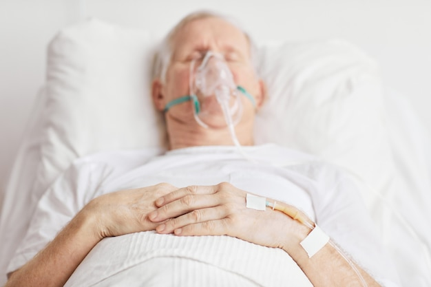 Close up of sick senior man lying in hospital bed with focus on iv drip needle in hand, copy space