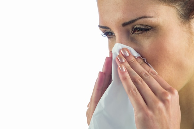 Close-up of sick woman with tissue on mouth