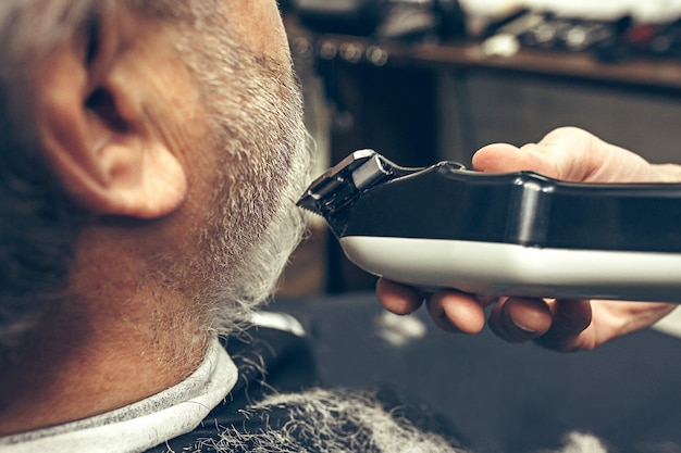 クローズアップ側背面ビューハンサムなシニアのひげを生やした白人男性ひげグルーミング現代の理髪店で。