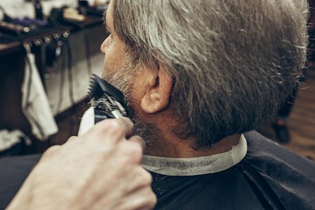 Close-up side back view handsome senior bearded caucasian man getting beard grooming in modern barbershop.