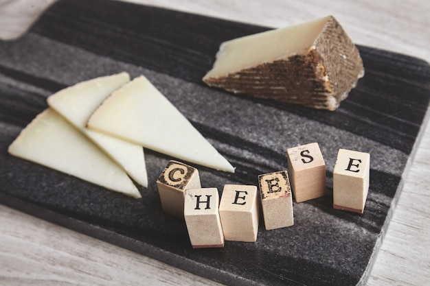 Close up side focused letters cheese ahead unfocused goat cheese on marble stone board isolated on wooden blank table