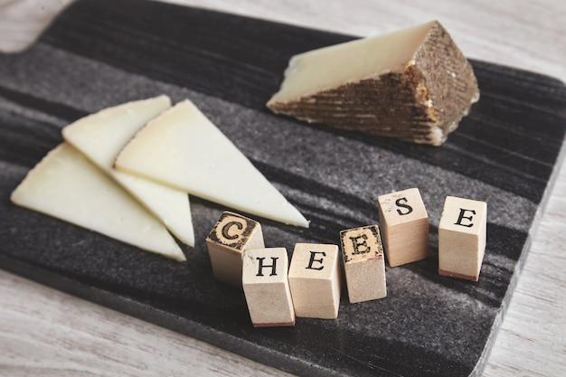 Крупным планом сфокусированные буквы сыр впереди несфокусированный козий сыр на мраморной каменной доске, изолированной на деревянном пустом столе