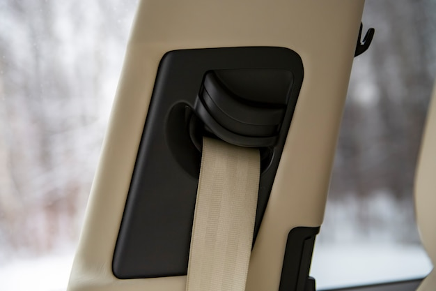 Close up side pillar with a light-colored seat belt in a modern car