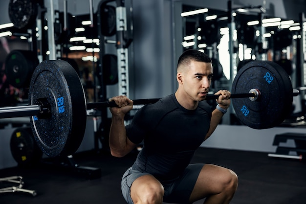 Close up side portrait of a male fitness trainer in grey sportswear doing squats using a barbell in a gym