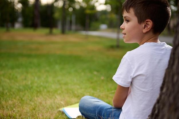 屋外で彼の学校のレクリエーションを楽しんで、目をそらしている幸せで気が散っている男子生徒のクローズアップの側面の肖像画。学校での初日の後、都市公園で休んでいる愛らしい子供