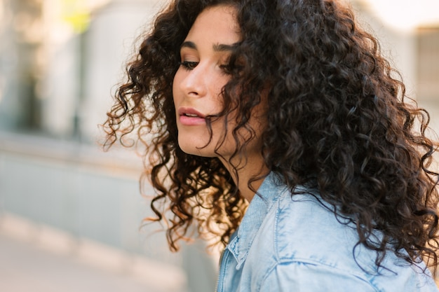 Close up side portrait of young curly woman leaning against a wall outside