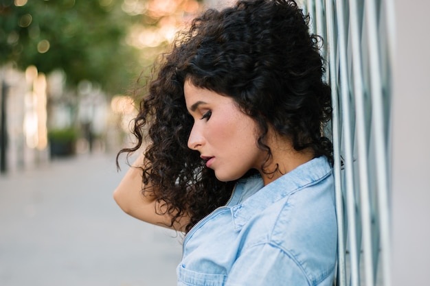 Close up side portrait of young curly woman leaning against a wall in the street