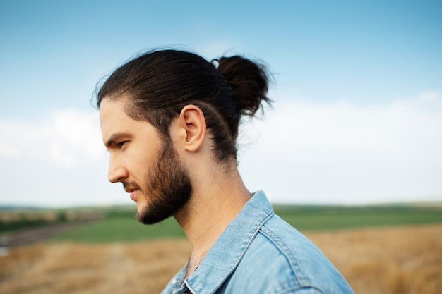 Close-up side portrait of young hipster guy with ponytail hairstyle.