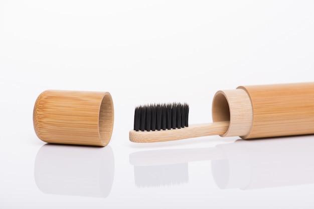 白い背景で隔離のキャップの黒い歯ブラシと木製のクラフトトリップケースカバーに詰められた環境に優しい竹のクローズアップ側面プロファイルマクロビュー写真