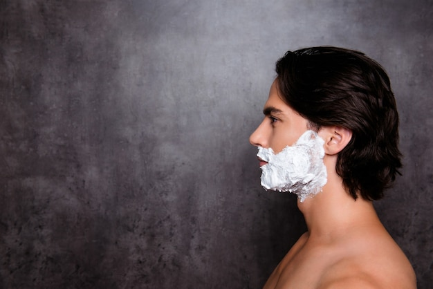 Close up side profile of man with white foam on his face