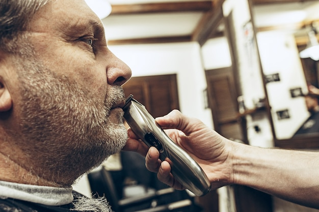 Close-up side profile view portrait of handsome senior bearded caucasian man getting beard grooming in modern barbershop.