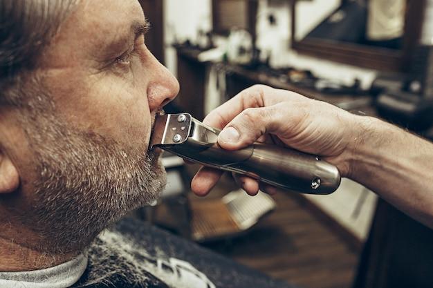 モダンな理髪店でひげの手入れをしているハンサムなシニアのひげを生やした白人男性のクローズアップ側縦断ビューの肖像画。