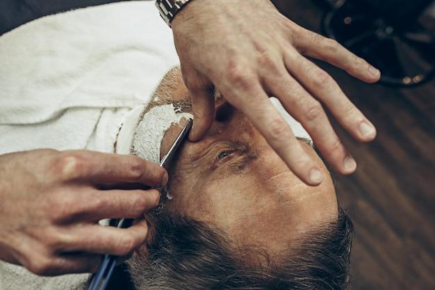クローズアップ側トップビューハンサムなシニアのひげを生やした白人男性ひげグルーミング現代の理髪店で。ストレートかみそりを使ってひげの散髪をする美容師。理髪店のコンセプトです。