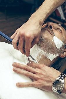 クローズアップ側トップビューハンサムなシニアのひげを生やした白人男性ひげグルーミング現代の理髪店で。