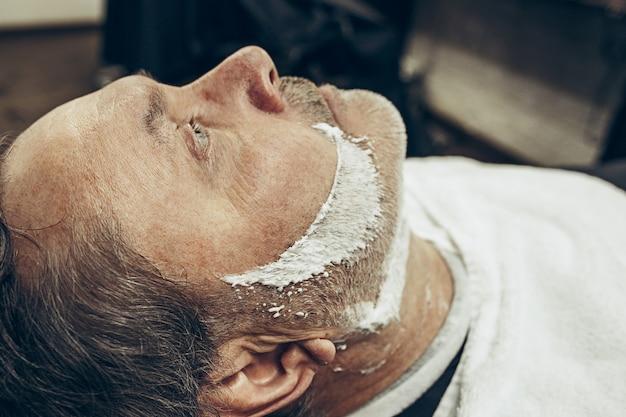 クローズアップ側トップビューハンサムなシニアひげを生やした白人男は現代の理髪店でひげの手入れをしています。