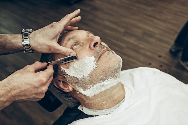 Close-up side top view handsome senior bearded caucasian man getting beard grooming in modern barbershop. hairdresser serving client, making beard haircut using straight razor. barber shop concept.