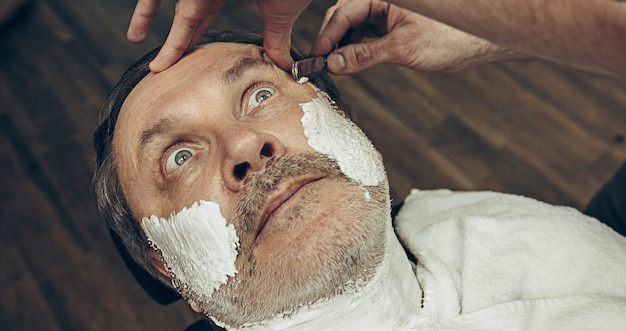 Close-up side top view handsome senior bearded caucasian man getting beard grooming in modern barbershop.