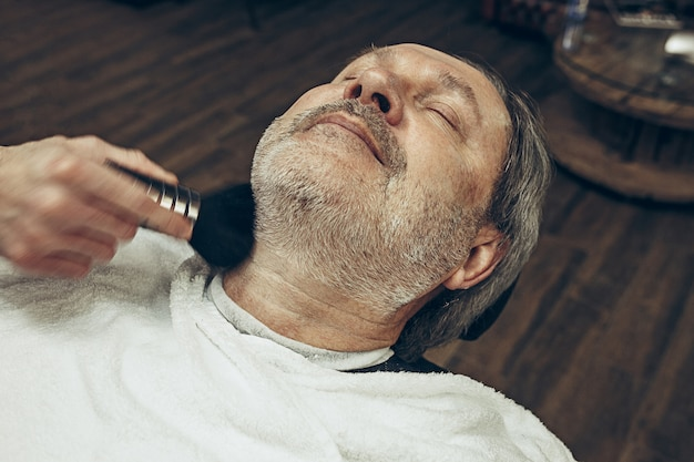Close-up side top view handsome senior bearded caucasian man getting beard grooming in modern barbershop.