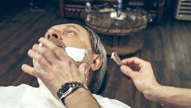 Uomo caucasico barbuto senior bello laterale superiore di vista superiore del primo piano che ottiene governare barba nel parrucchiere moderno.