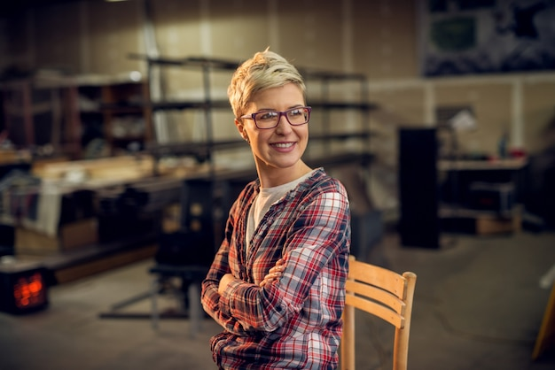 Close up side view of blonde short hair hardworking woman sitting on the chair in the workshop and posing while looking far away