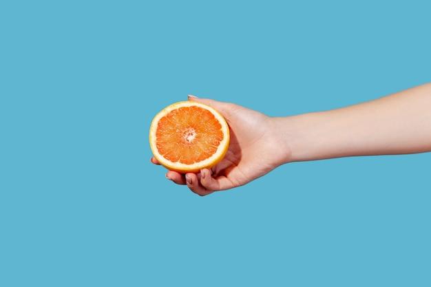 熟したジューシーなグレープフルーツオレンジまたはザボンの半分を持っている女性の手の側面図を閉じる