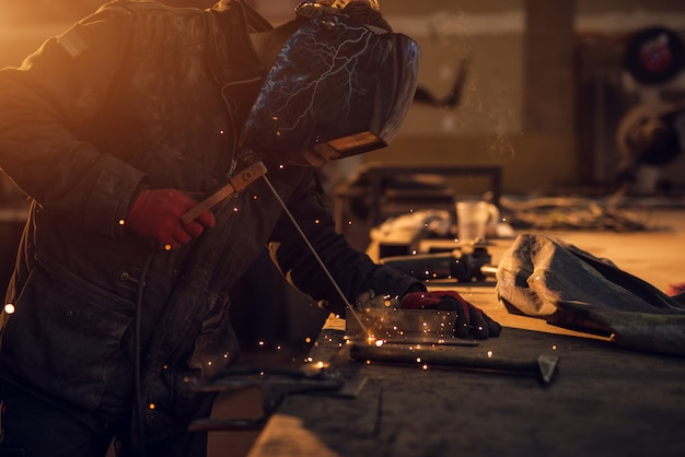 Close up side view of focused professional welder with protection mask working at the table in a sunny fabric workshop