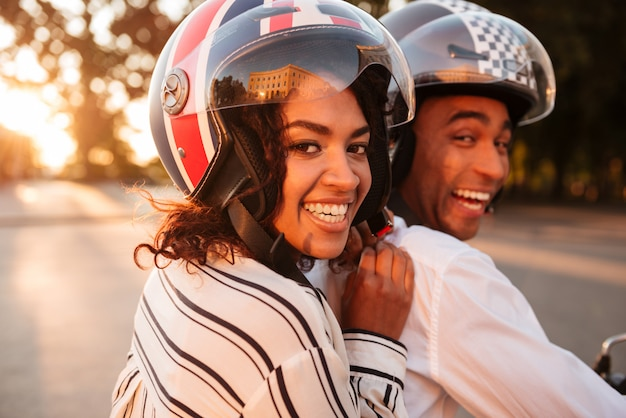 Close up side view image of happy african couple rides on modern motorbike outdoors and looking at the camera
