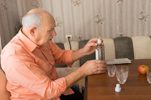 Крупным планом вид сбоку серьезного старика, держащего бутылку водочного вина на деревянном столе