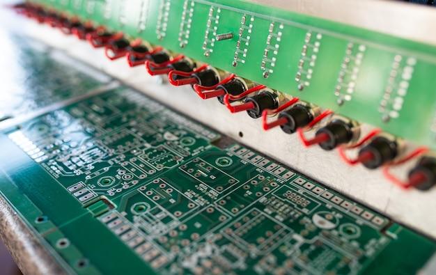 Крупным планом вид сбоку сложных микросхем и зеленых плат на панели, соединенных друг с другом с помощью красных проводов при производстве военной техники. концепция секретной технологии