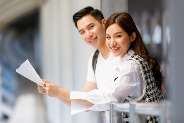 Close-up side view portrait of cute smiling young asian couple tourists standing and holding paper map on flyover footbridge looking camera. selective focus at a woman with blurred man and background