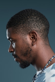 Close up side view portrait of handsome africanamerican man against blue focus on profile outline