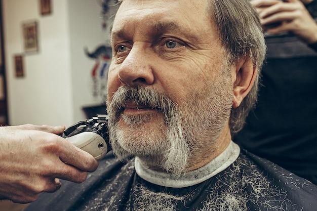Close-up side view portrait of handsome senior bearded caucasian man getting beard grooming in modern barbershop.