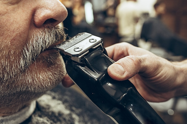 Close-up side view portrait of handsome senior bearded caucasian man getting beard grooming in modern barbershop.
