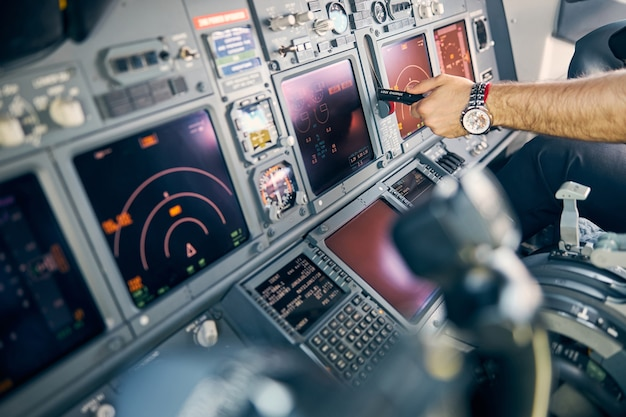 Close up side view portrait of man pilot controlling flying on the dashboard panel in cockpit