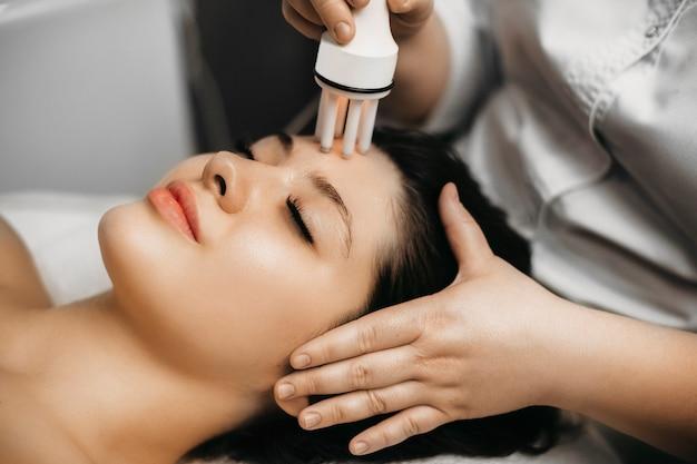Крупным планом вид сбоку портрет красивой брюнетки, делающей омолаживающую мезотерапию на лице в оздоровительном спа-центре.