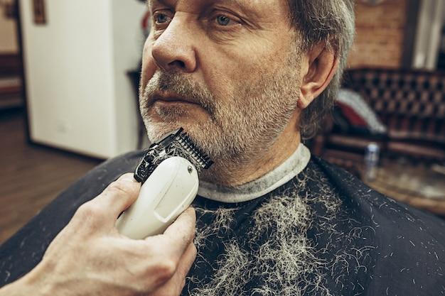 ハンサムなシニアのクローズアップ側ビュー肖像画ひげを生やした白人男性ひげグルーミング現代の理髪店で。